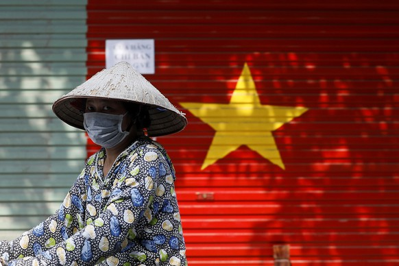 epa09352986 A woman wears a face mask as she rides bicycle at a street in Hanoi, Vietnam, 19 July 2021. Vietnam tightened restrictions in 19 provinces, after nearly 6,000 new COVID-19 cases were reported in one day in the country.  EPA/LUONG THAI LINH