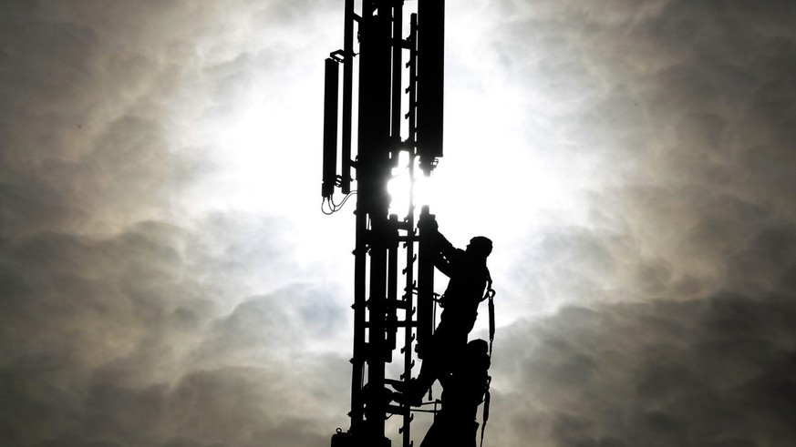 Two workers are silhouetted as they fix a mobile phone pole against the sun in Duisburg, western Germany, Tuesday Oct.26,2010. The advanced use of mobile data with 3 G and the for the future planned 4G standard make it necessary to build more poles all around Germany.(AP Photo/Frank Augstein)
