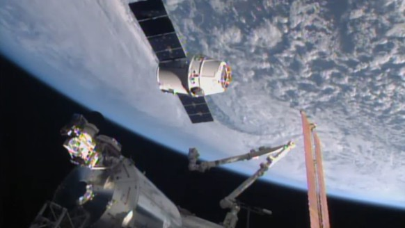 In this image from NASA-TV shows the SpaceX Dragon-6 resupply capsule Friday April 17, 2015 as it holds at the grapple point, 10 meters from the International Space Station as they cross over the Asia. (NASA-TV via AP)