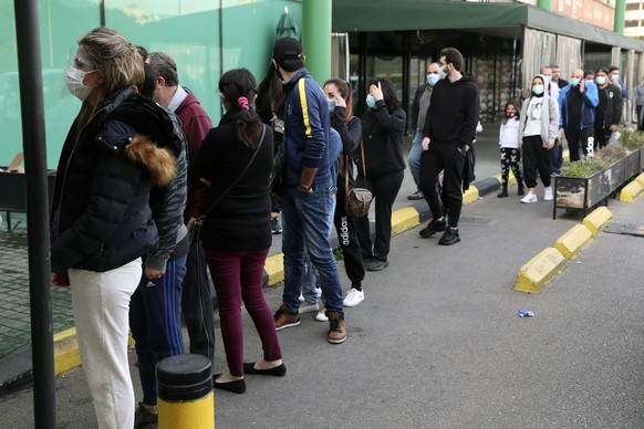 People line up to enter a supermarket, in Beirut, Lebanon, Monday, Jan. 11, 2021. Panic buyers swarmed supermarkets after reports the government planned to also order them shut in the tightened lockdown. Long lines formed outside chain supermarkets, sparking fear the crowds could further spread the virus. (AP Photo/Bilal Hussein)