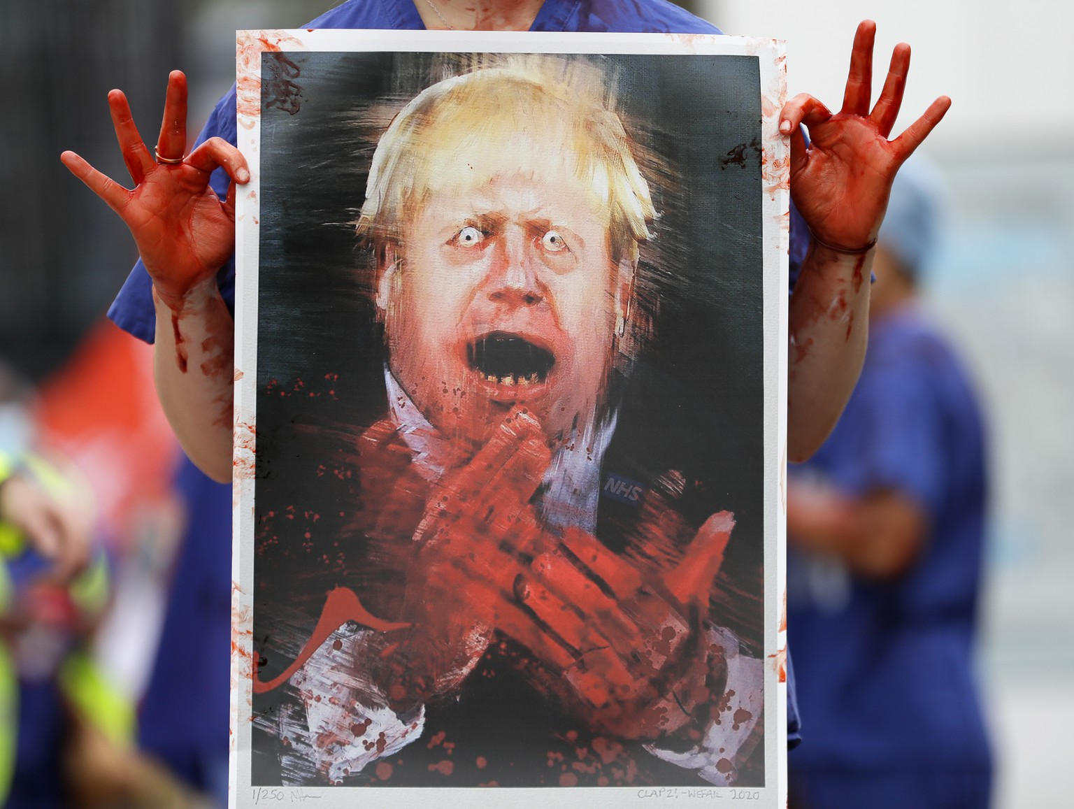A nurse holds a painting of Prime Minister Boris Johnson clapping with blood on his hands as part of a demonstration of NHS workers at hospitals across London to demand a 15 per cent pay rise by the government in London, Wednesday, Aug. 26, 2020.(AP Photo/Kirsty Wigglesworth)