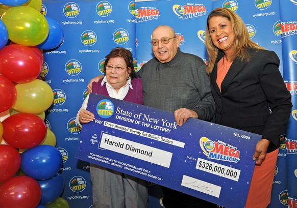 Harold Diamond and his wife Carol receive their ceremonial check from Yolanda Vega at the Valero gas station in the Town of Wallkill, N.Y., on Monday, Jan. 12, 2015. The 80-year-old retired school principal is the sole winner of the Nov. 4 $326 million Mega Millions jackpot, the biggest prize in New York Lottery history. (AP Photo/Times Herald-Record, John DeSanto)