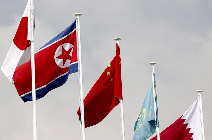epa04394980 A picture made available on 11 September 2014 shows the North Korean flag (2-L) together with other flags at the Athletes' village of the 17th Asian games in Incheon, South Korea, 26 August 2014. Before the arrival of the first North Korean athletes, all the national flags were removed and replaced by flags with the logo of the Asian Games and the Olympic Council of Asia, after protests by local conservative groups in Incheon, on 10 September 2014.  EPA/JEON HEON-KYUN