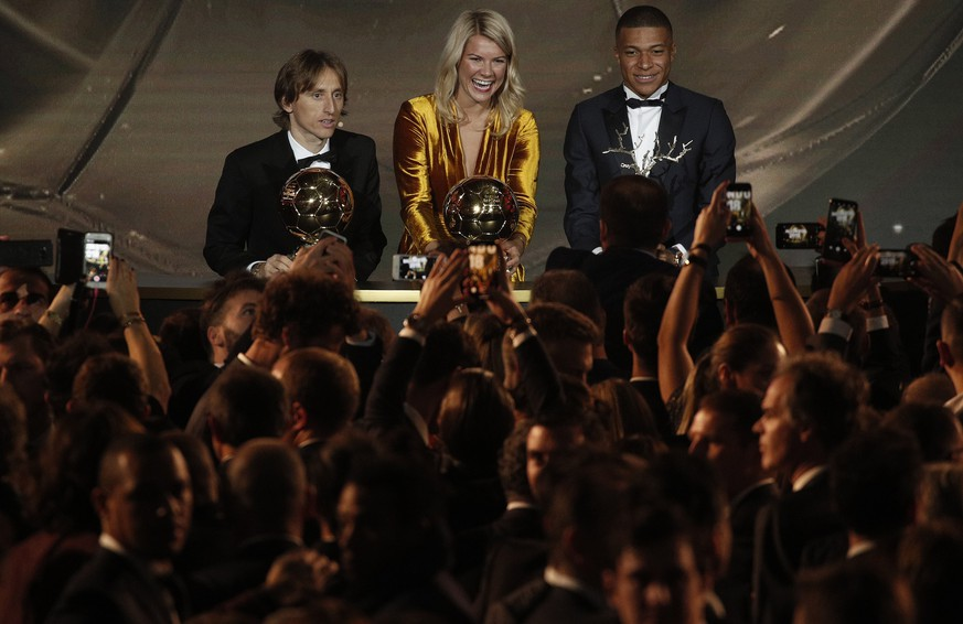 epa07206920 (L-R)  Real Madrid's Luka Modric Olympique Lyonnais' Ada Hegerberg and Paris St Germain's Kylian Mbappe holds their 'Ballon d'Or' (Golden ball) trophies during the ceremony rewarding the best European footballer of the year in Paris, France, 03 December 2018.  EPA/YOAN VALAT