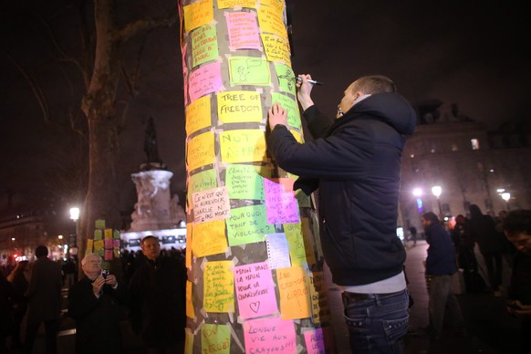 epa04550232 A man writes a note on a 'tree of freedom' covered with messages as people light candles as they gather to commemorate the victims and condemn the killings at the French magazin Charly Hebdo, on the Place de la Republique in Paris, France, late 07 January 2015. Ten journalists and two policemen were killed in the shooting by a terrorists attack at the Charlie Hebdo headquarters in Paris.  EPA/Fredrik Von Erichsen