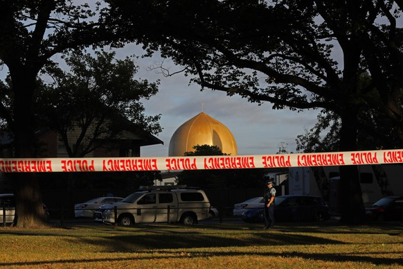 FILE - In this March 17, 2019 file photo, a police officer stands guard in front of the Masjid Al Noor mosque in Christchurch, New Zealand, where one of two mass shootings occurred. According to a report released Wednesday, March 18, 2020, by an organization that tracks far-right extremists, a recent surge in white nationalism in the U.S. has led to a growing threat of violence by factions that embrace bloodshed and advocate for a race war.  The man accused of attacking two mosques in Christchurch, New Zealand, and killing 51 people in March 2019 devoted a section of his manifesto to the concept of accelerationism, a fringe philosophy that promotes mass violence to fuel society's collapse. (AP Photo/Vincent Yu, File)