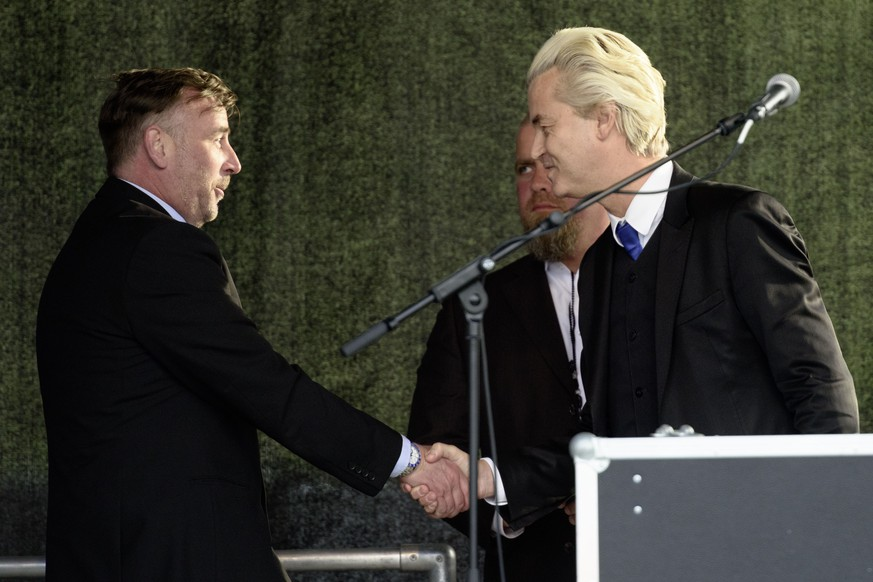 DRESDEN, GERMANY - APRIL 13: Right-wing Dutch politician Geert Wilders (R) shakes the hand of Pegida organizer Lutz Bachmann (L) at the rally of the Pegida movement at another of their weekly protests on April 13, 2015 in Dresden, Germany. A large number of supporters and opponents are expected to attend the rally, which will feature Dutch right-wing politician Geert Wilders as a guest speaker. The Pegida movement, which originally emerged as a grass-roots effort with aims to curb immigration, among other issues, splintered into two camps earlier this year and the movement is seeking to regain its earlier momentum. (Photo by Jens Schlueter/Getty Images)