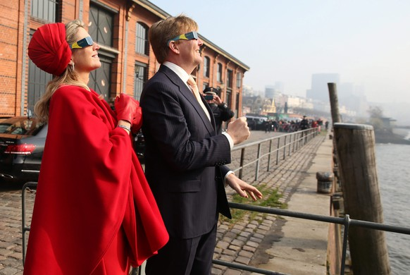 epa04670828 Queen Maxima and King Willem-Alexander of the Netherlands look at the solar eclipse through special glasses at the Fish Market inHamburg, Germany, 20 March 2015. The royal couple is on a two-day working visit of Northern Germany. A Partial Solar Eclipse is seen in Europe, northern and eastern Asia and northern and western Africa on 20 March with the eclipse starting at 07:41 UTC and ending at 11:50 UTC.  EPA/CHRISTIANCHARISIUS