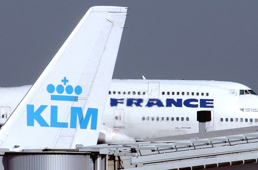 An Air France jumbo jet rolls behind the tail of a KLM Royal Dutch airliner at Charles de Gaulle airport in Roissy, north of Paris, Tuesday, September 30, 2003. The two airlines announced Tuesday a landmark partnership to create Europe's largest airline group, in a deal they say will define the future of European aviation. (KEYSTONE/AP Photo/Remy de la Mauviniere)