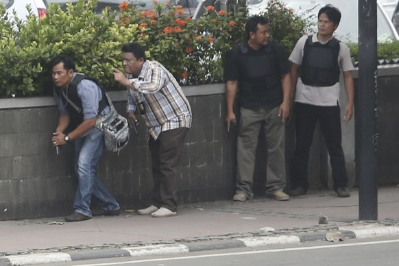 Police officers take their positions as they search buildings near the site of an explosion in Jakarta, Indonesia Thursday, Jan. 14, 2016. Attackers set off explosions at a Starbucks cafe in a bustling shopping area of downtown Jakarta and waged gun-battles with police Thursday, leaving bodies in the streets as office workers watched in terror from high-rise windows. (AP Photo/Tatan Syuflana)