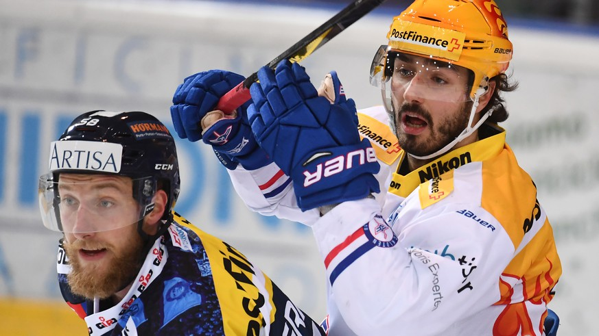 Ambri's player Jesse Zgraggen, left, fights for the puck with Kloten's Topscorer Denis Hollenstein, right, during the preliminary round game of National League Swiss Championship 2017/18 between HC Ambri Piotta and EHC Kloten, at the ice stadium Valascia in Ambri, Switzerland, Saturday, November 18, 2017. (PPR/Gabriele Putzu)