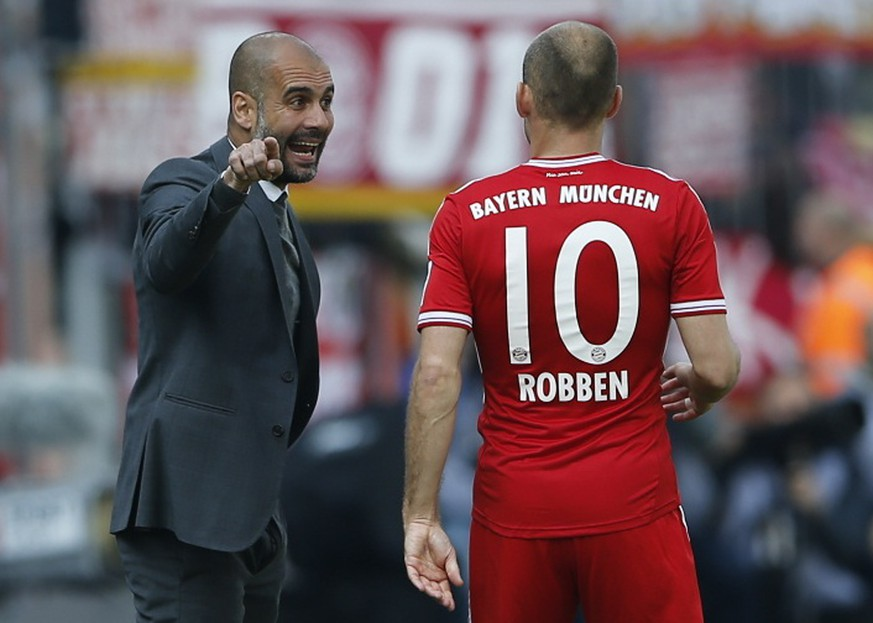 Bayern Munich's coach Pep Guardiola speaks with his player Arjen Robben (R) during the German first division Bundesliga soccer match against Eintracht Braunschweig in Berlin April 19, 2014.   REUTERS/Fabrizio Bensch (GERMANY  - Tags: SPORT SOCCER HEADSHOT) DFL RULES TO LIMIT THE ONLINE USAGE DURING MATCH TIME TO 15 PICTURES PER GAME. IMAGE SEQUENCES TO SIMULATE VIDEO IS NOT ALLOWED AT ANY TIME. FOR FURTHER QUERIES PLEASE CONTACT DFL DIRECTLY AT + 49 69 650050.