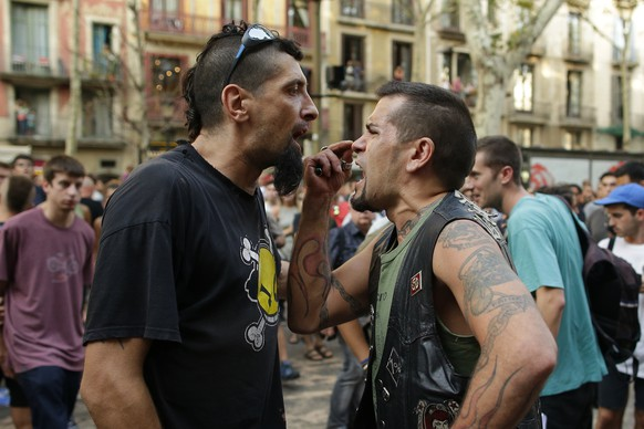 A counter protester and a far-right protester argue during a gathering after a van attack in Barcelona, Spain, Friday Aug. 18, 2017. Police on Friday shot and killed five people carrying bomb belts who were connected to the Barcelona van attack, as the manhunt intensified for the perpetrators of Europe's latest rampage claimed by the Islamic State group. (AP Photo/Manu Fernandez)