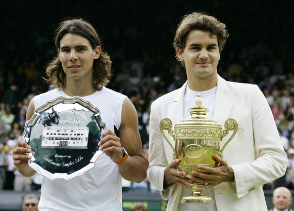 Defending champion Roger Federer, right, holds the winners trophy with runner up Rafael Nadal of Spain after the Men's Singles final on the Centre Court at Wimbledon, Sunday July 9, 2006. Federer won the match 6-0, 7-6, 6-7, 6-3.    (AP Photo/Anja Niedringhaus)