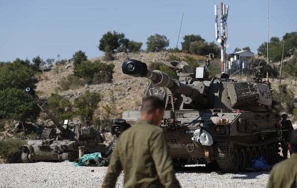 epa07792033 Israeli soldiers stand next to their armoured fighting vehicle (AFV) at the Israeli-Syrian border, in the Golan Heights, north of Israel, 25 August 2019. The Israel Defense Forces (IDF) confirmed on the day that overnight its Air Force had struck Iranian Quds Force targets in Syria. In reactions to the incident, the Israeli deployed artillery units and the Iron Dome at the border with Syria.  EPA/ATEF SAFADI
