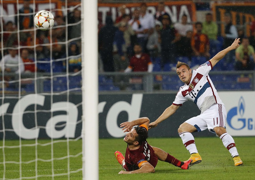 Bayern Munich's Xherdan Shaqiri (R) shoots to score as he is challenged by AS Roma's Kostas Manolas during their Champions League soccer match at the Olympic stadium in Rome October 21, 2014. REUTERS/Alessandro Bianchi (ITALY - Tags: SPORT SOCCER TPX IMAGES OF THE DAY)