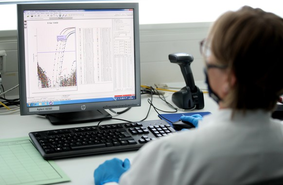 epa08715581 An employee analyses a positive corona test on her computer at the Chemical and Veterinary Investigation Office (CVUA) in Muenster, Germany, 02 October 2020. In the laboratory for veterinary samples of the Chemical and Veterinary Investigation Office, up to 500 PCR examinations for the coronavirus are carried out daily.  EPA/FRIEDEMANN VOGEL