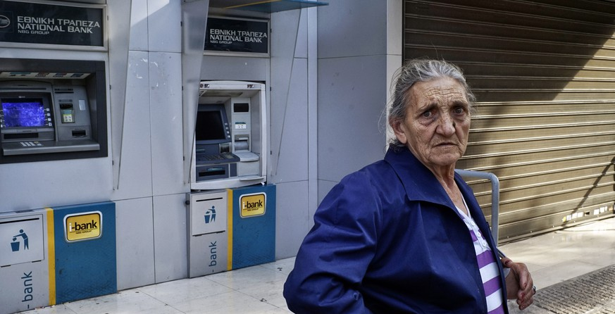 ATHENS, GREECE - JUNE 29: A pensioner stands outside of a branch of the National Bank of Greece hoping to draw her pension on June 29, 2015 in Athens, Greece. Greece closed its banks and imposed capital controls on Sunday to check the growing strains on its crippled financial system, bringing the prospect of being forced out of the euro into plain sight.   (Photo by Milos Bicanski/Getty Images)
