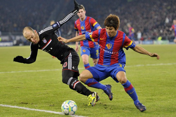 Bayern's Arjen Robben, left, fights for the ball against Basel's Joo Ho Park, right, during the Champions League round of sixteen first leg match between Switzerland's FC Basel and Germany's FC Bayern Munich in the St. Jakob-Park stadium in Basel, Switzerland, on Wednesday, February 22, 2012. (KEYSTONE/Georgios Kefalas)