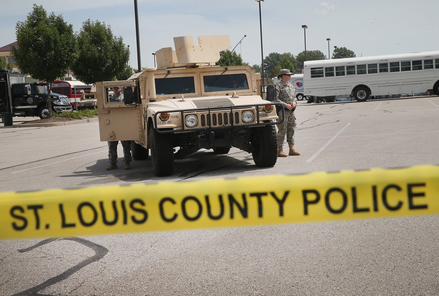 FERGUSON, MO - AUGUST 21:  Military police with the Missouri Army National Guard stand guard at the police command center which was established to direct security operations following unrest after the recent death of Michael Brown on August 21, 2014 in Ferguson, Missouri. Brown was shot and killed by a Ferguson police officer on August 9. Missouri Gov. Jay Nixon ordered the withdrawal of the National Guard four days after they were deployed to help during the protests following the shooting death of Michael Brown.  (Photo by Scott Olson/Getty Images)