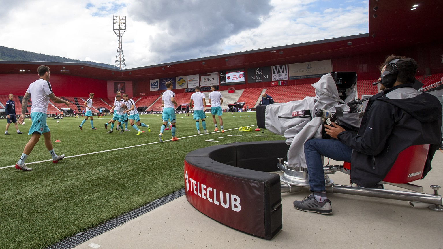 Xamax's players warm up near a camera of Teleclub broadcaster, prior the Super League soccer match of Swiss Championship between Neuchatel Xamax FCS and FC Thun, behind closed doors at the Stade de la Maladiere stadium, in Neuchatel, Switzerland, Saturday, June 20, 2020.All Super League soccer matches of Swiss Championship are played to semi behind closed doors (only 300 persons can be present in the stadium) due to preventive measure against a second wave of the coronavirus COVID-19. (KEYSTONE/Salvatore Di Nolfi)