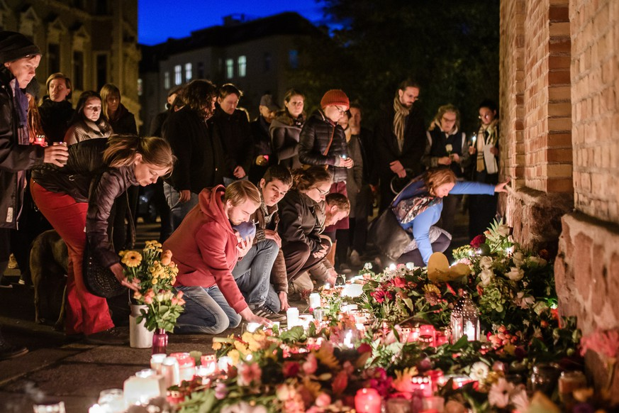 epaselect epa07911071 People mourn in front of the synagogue in Halle (Saal), Germany, 10 October 2019.  According to the police two people were killed on 09 October in shootings in front of the synagogue and a Kebab shop in the Paulus district of Halle in the East German federal state of Saxony-Anhalt.  EPA/CLEMENS BILAN