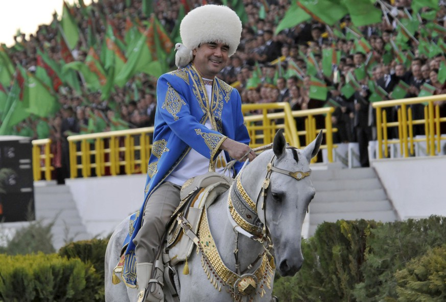 FILE - In this Saturday April 23, 2011 file photo, Turkmenistan's President Gurbanguli Berdymukhamedov smiles as he rides a horse with a dove on his shoulder at a ceremony in the capital Ashgabat, Turkmenistan. When the Soviet Union collapsed, a clutch of nations emerged in the vast areas of steppe and mountains between Russia's southern border down to Iran and Afghanistan. Berdymukhamedov is regularly filmed and photographed riding horses, driving racing cars (and winning races in them), flying helicopters, cycling, jogging and doing weights. (AP Photo/Alexander Vershinin, File)