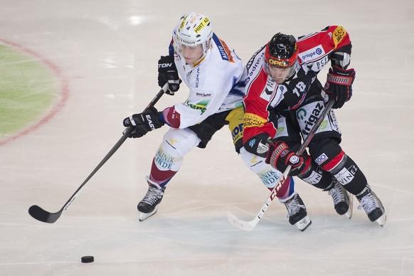 Le joueur biennois Kevin Fey, gauche, lutte pour le puck avec le joueur fribourgeois Marc-Antoine Pouliot, droite, lors du match du championnat suisse de hockey sur glace de National League A, entre le HC Fribourg-Gotteron et le EHC Biel-Bienne, ce vendredi 31 octobre 2014 a la patinoire de la BCF Arena de Fribourg. (KEYSTONE/Jean-Christophe Bott)