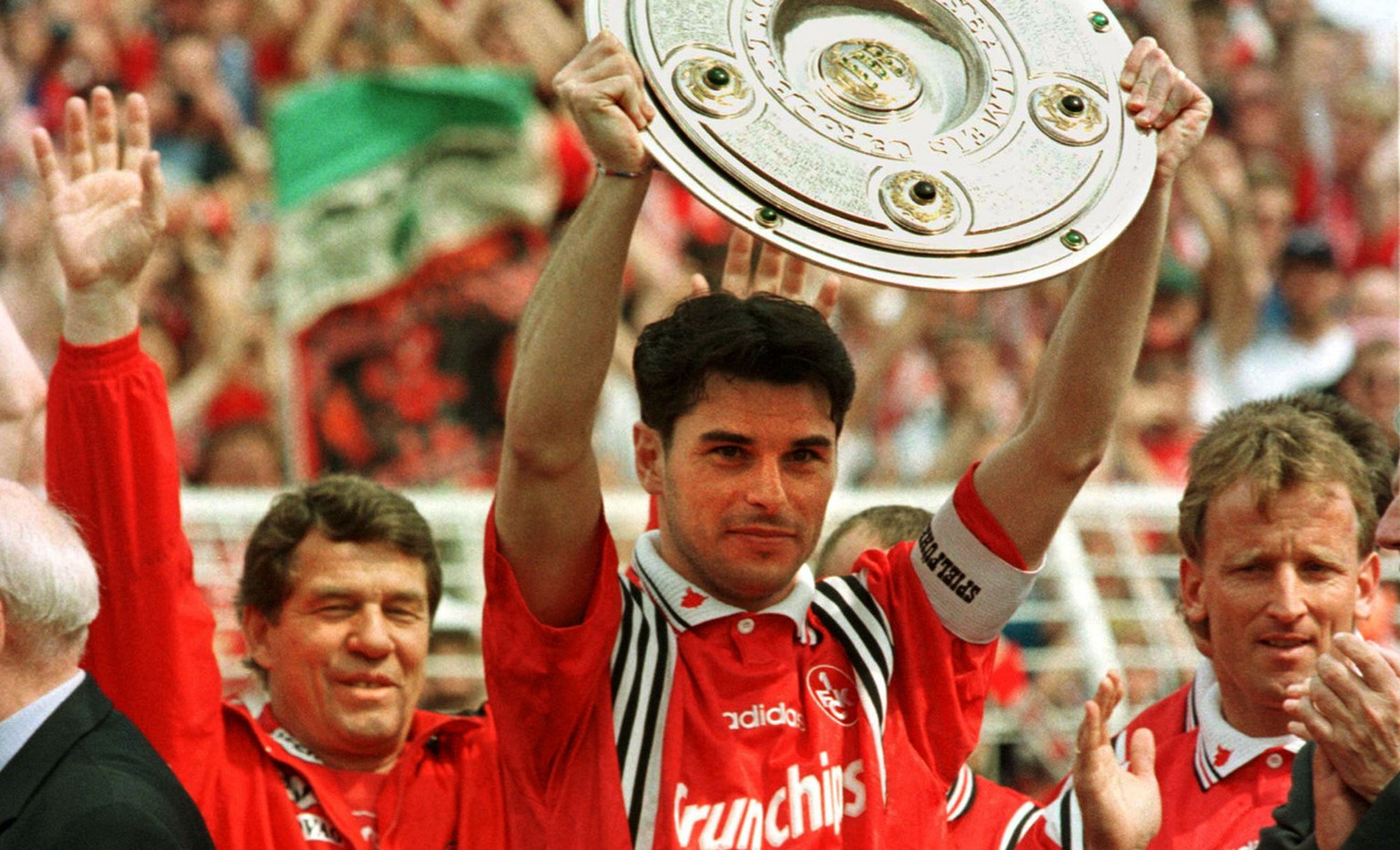 Team captain of German soccer champion Kaiserslautern, Ciriaco Sforza, displays the trophy in Hamburg's Volkspark Stadium on Saturday May 9, 1998, prior to the season's last match Hamburg vs Kaiserslautern. Kaiserslautern decided the chamiponship already last week but the trophy was traditionally handed over on the last match. Left coach Otto Rehhagel, right Andreas Brehme. (AP Photo/Michael Probst)