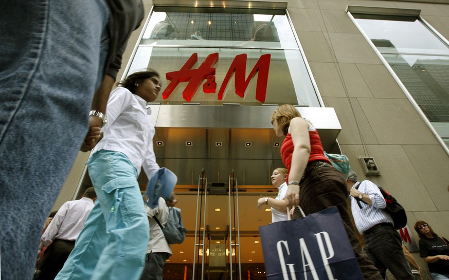 Pedestrians walk past the Fifth Avenue store owned by Stockholm-based fashion retailer Hennes and Mauritz (H and M) Wednesday, June 21, 2006, in New York. HandM posted a 12 percent increase in second-quarter profit Wednesday, helped by a spike in sales in May but capped by higher marketing costs. HandM said that it plans to open approximately 100 stores during the remaining part of the financial year, mainly in the U.S., Spain, France, Britain, Canada and Germany. During spring 2007, the company had signed contracts for one full-range store each in Shanghai and in Hong Kong, the company's first stores in the Far East. (KEYSTONE/AP Photo/Kathy Willens)