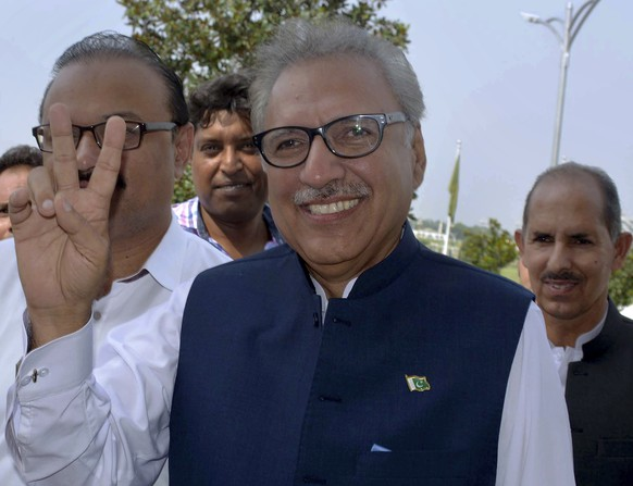 Arif Alvi, presidential candidate from the ruling Pakistan Tehreek-e-Insaf Party, makes a victory sign upon arrival at parliament in Islamabad, Pakistan, Tuesday, Sept. 4, 2018. Polling started at Pakistan's parliament and four provincial legislatures to indirectly elect the country's new President, a process which will strengthen grip of the ruling party on power, as its nominee Alvi is expected to easily become new ceremonial head of the state. (AP Photo/Anjum Naveed)