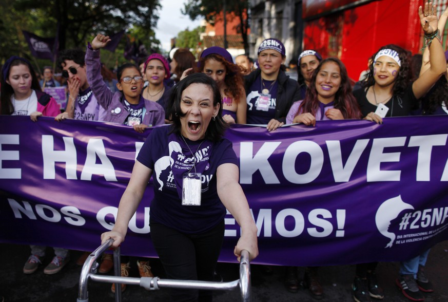 A woman using a walker leads a march marking the International Day for the Elimination of Violence against Women, in Asuncion, Paraguay, Saturday, Nov. 25, 2017. According to officials there is at least one femicide reported per week in Paraguay. (AP Photo/Jorge Saenz)