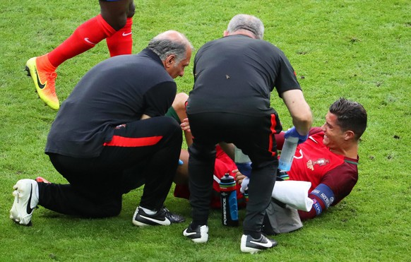 epa05419074 Cristiano Ronaldo (R) of Portugal receives medical assistance during the UEFA EURO 2016 Final match between Portugal and France at Stade de France in Saint-Denis, France, 10 July 2016.  (RESTRICTIONS APPLY: For editorial news reporting purposes only. Not used for commercial or marketing purposes without prior written approval of UEFA. Images must appear as still images and must not emulate match action video footage. Photographs published in online publications (whether via the Internet or otherwise) shall have an interval of at least 20 seconds between the posting.)  EPA/SRDJAN SUKI   EDITORIAL USE ONLY