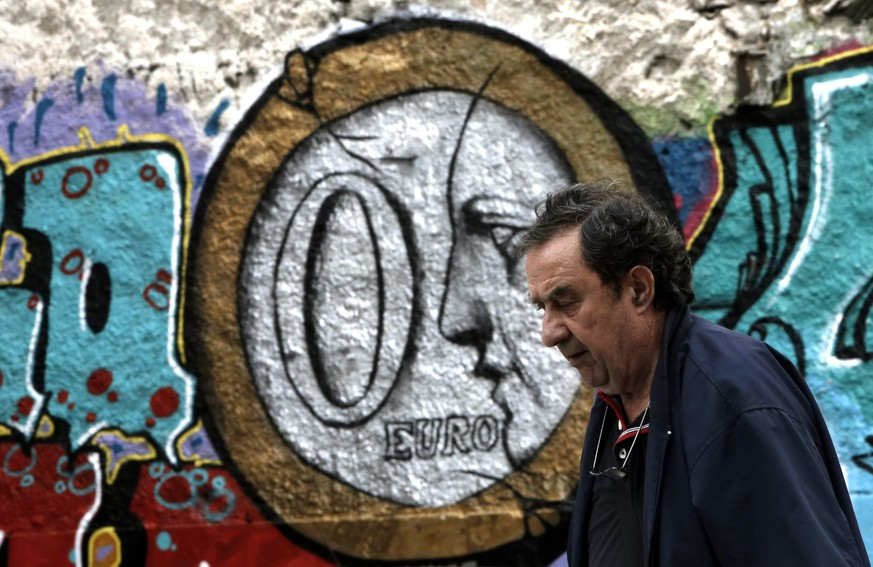 epaselect epa04813838 A man walks in front of a wall covered with graffiti, depicting a zero euro coin in central Athens, Greece, 22 June 2015. The negotiations between the Greek government and the creditors will peak on later in the day in Brussels with the view to bridging the differences in taxation and early pensions and reaching an agreement.  EPA/YANNIS KOLESIDIS