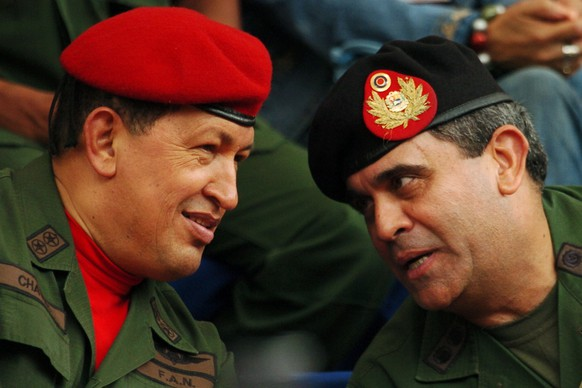 FILE - In this  Aug. 11, 2006 file photo, Venezuela's President Hugo Chavez, left, and his Defense Minister Raul Baduel attend the military reserve changing of command ceremony in Caracas, Venezuela, The former Defense Minister has died on Oct. 12, 2021, after contracting COVID-19 inside the prison where he was being held, accused of plotting a coup against Venezuelan President Nicolas Maduro. (AP Photo/Gregorio Marrero, File)