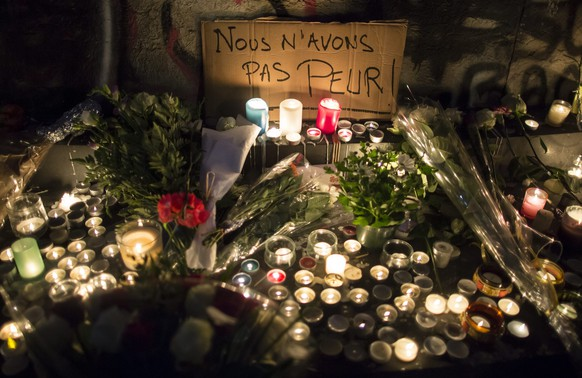 epa05025391 People place flowers and light candles in tribute for the victims of the 13 November Paris attacks at the foot of the statue on Place de la Republique in Paris, France, 14 November 2015. At least 120 people have been killed in a series of attacks in Paris on 13 November, according to French officials. Sign reads in French 'We are not afraid'.  EPA/IAN LANGSDON