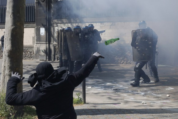 A hooded youth throws a bottle during a clash with French riot police to protest against the French labour law proposal during the May Day labour union march in Paris, France, May 1, 2016.  REUTERS/Philippe Wojazer