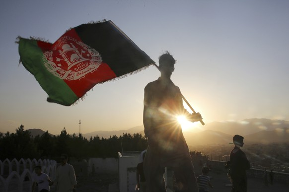 FILE - In this Aug. 19, 2019, file photo, a man waves an Afghan national flag during Independence Day celebrations in Kabul, Afghanistan. Washington