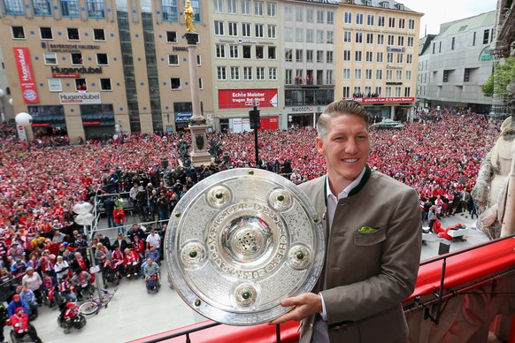 Bastian Schweinsteiger of Bayern Munich holds the German Championship  winners trophy as the team celebrate winning the German Championship title on the town hall balcony at Marienplatz in Munich, Germany May 24, 2015.  REUTERS/Alexander Hassenstein/Pool