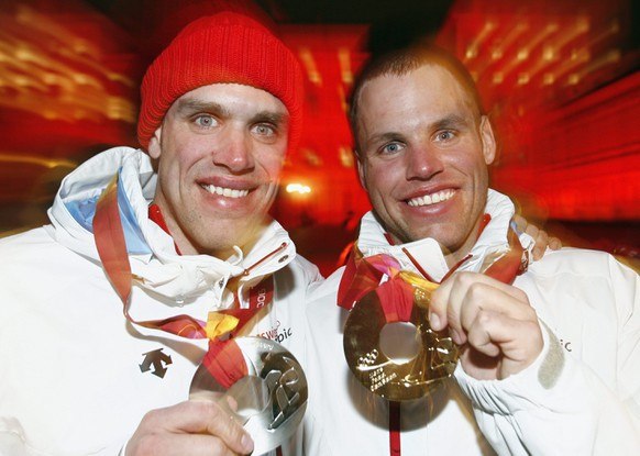First placed Swiss Philipp Schoch, right, and his brother Simon Schoch show the gold and silver medals they won in today's Snowboard Men's Parallel Giant Slalom after the medal ceremony on Piazza Castello in Turin, Italy, Wednesday, February 22, 2006, during the XX. Turin 2006 Olympic Winter Games. (KEYSTONE/Alessandro della Valle)