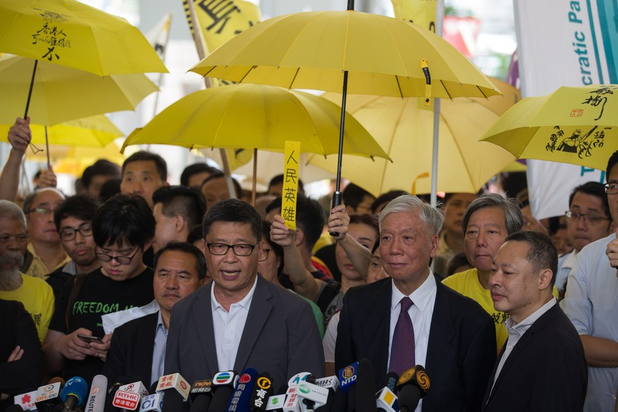 epa07524296 Occupy Central activists Chan Kin-man (L, front) Reverend Chu Yiu-ming (C, front) and Benny Tai (R, front) speak to the media before their sentencing, outside West Kowloon Magistrates Court in Hong Kong, China, 24 April 2019. Key leaders of the Occupy protest movement called on their supporters to continue their fight as most of the leaders hinted that they expect to be in prison for an extended period of time following the sentencing. The Umbrella movement, which occurred concurrently with Occupy Central, ran for 79 days in 2014.  EPA/JEROME FAVRE