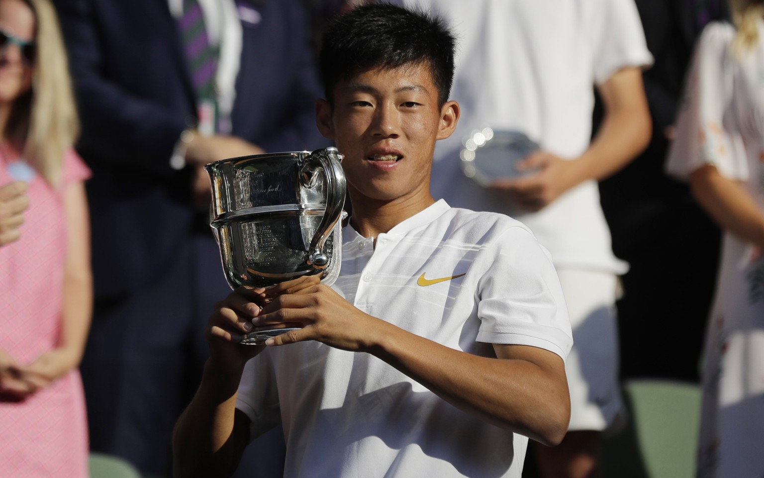 Tseng Chun Hsin of Taiwan kisses the trophy after defeating Jack Draper of Britain in the boys' singles final at the Wimbledon Tennis Championships in London, Sunday July 15, 2018. (AP Photo/Ben Curtis)