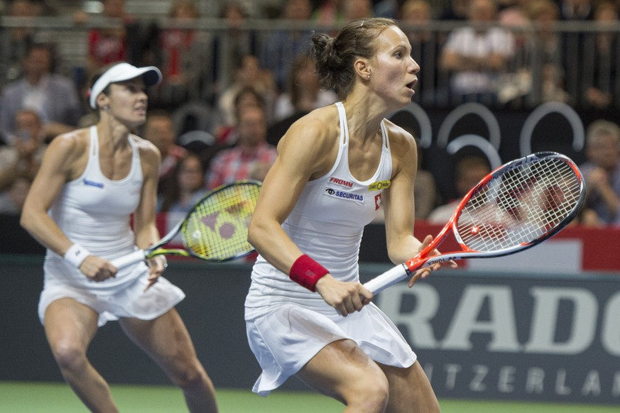Switzerland's double team members Martina Hingis, left, and Viktorija Golubic, right, in action against the double team of the Czech Republic with Karolina Pliskova and Lucie Hradecka, unseen, during their World Group semifinal Fed Cup tennis match between Switzerland and the Czech Republic, in Lucerne, Switzerland, Sunday, April 17, 2016. (KEYSTONE/Urs Flueeler)