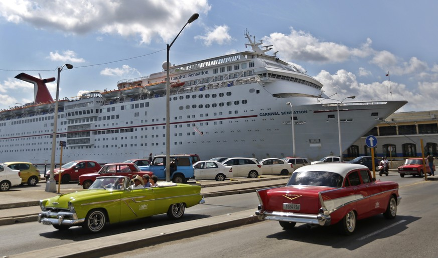 epa07531084 Two classic American cars pass in front of a cruise ship anchored in the port of Havana, Cuba, 26 April 2019.  EPA/Yander Zamora