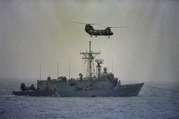 FILE - In this April 15, 1988 file photo, a U.S. Navy helicopter flies over the disabled U.S. frigate Samuel B. Roberts as she continues under tow, a day after she struck a mine, injuring 10 sailors and damaging the hull and engine room. During the Iran-Iraq war in the 1980s, Iran mined portions of the Persian Gulf and several commercial ships sank. In 1988, the USS Samuel B. Roberts struck a mine and nearly sank. That sparked a daylong naval battle between Iran and the U.S. in which American forces attacked two Iranian oil rigs and sank or damaged six Iranian vessels. (AP Photo, File)