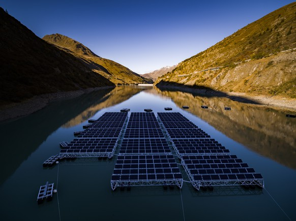 epa07906934 Floating barges with solar panels are pictured on the Lac des Toules, an alpine reservoir lake, in Bourg-Saint-Pierre, Switzerland, 08 October 2019 (issued 09 October 2019) Upon completion the floating solar panel station will consist of 36 floating barges featuring 2'240 square meters of solar cells targeting to deliver 800'000 kilowatt-hour per year, the annual power consumption of approximately 220 homes.  EPA/VALENTIN FLAURAUD PICTURE TAKEN WITH A DRONE ATTENTION: This Image is part of a PHOTO SET