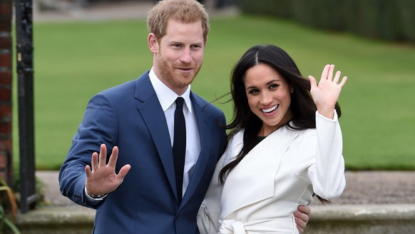 FILE - In this Nov. 27, 2017 file photo, Britain's Prince Harry and Meghan Markle pose for the media in the grounds of Kensington Palace in London, after announcing their engagement. The couple will wed on May 19. (Eddie Mulholland/Pool via AP)