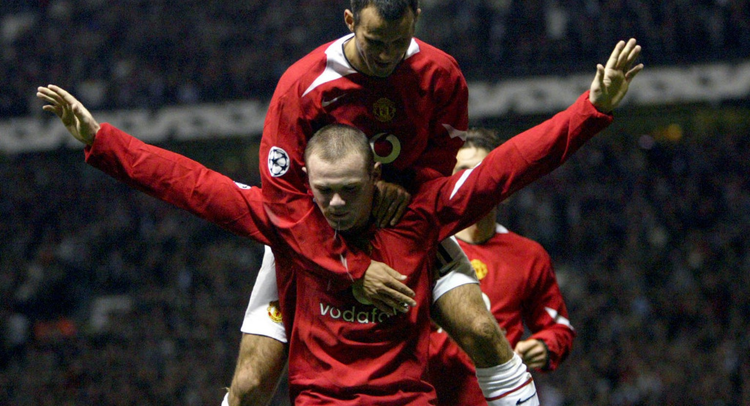 Manchester United's Wayne Rooney, center, is congratulated by teammate Ryan Giggs after scoring his second goal on his debut against Fenerbahce during their Champion's League group D soccer match at Old Trafford Stadium, Manchester England, Tuesday Sept. 28, 2004. (AP Photo/Jon Super)