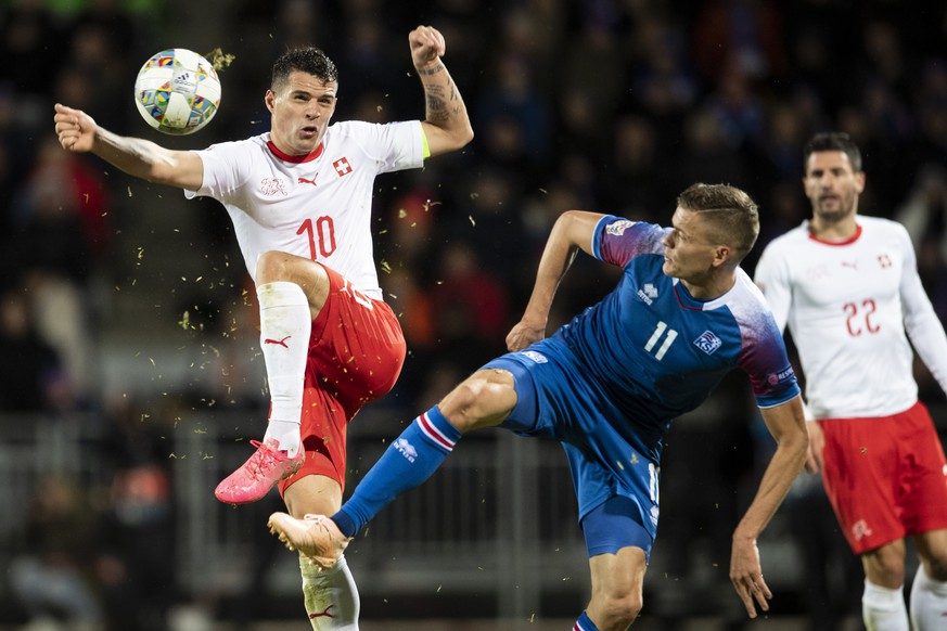 Switzerland's Granit Xhaka left, fights for the ball against Iceland's Alfred Finnbogason, right, during the UEFA Nations League soccer match between Iceland and Switzerland at the Laugardalsvoellur stadium in Reykjavik, Iceland, on Monday, October 15, 2018. (KEYSTONE/Ennio Leanza)