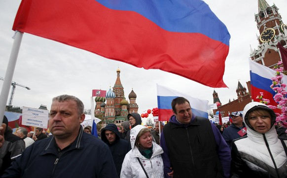 People walk with flags at Red Square during a May Day rally in Moscow May 1, 2015. International Workers' Day, also known as Labour Day or May Day, commemorates the struggle of workers in industrialised countries in the 19th century for better working conditions.  REUTERS/Maxim Zmeyev